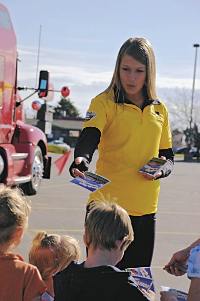 Kaiti Frickley handing out a postcard to children in Idaho Falls, Idaho